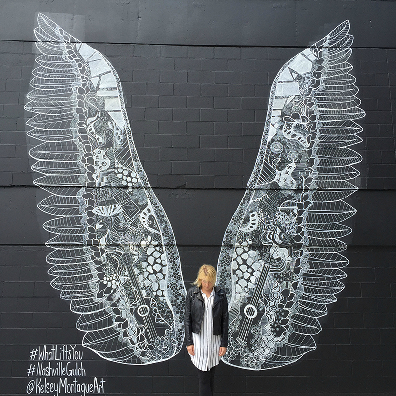 Girl standing in front of a pair of wings painted onto a black wall