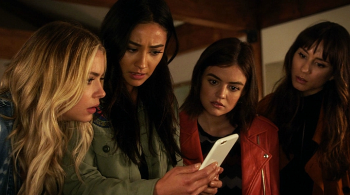 The girls looking at a text on Emily's phone