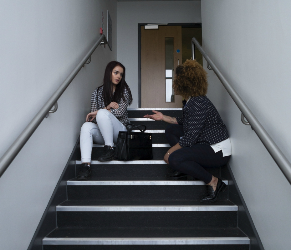 two girls are talking in a stairway
