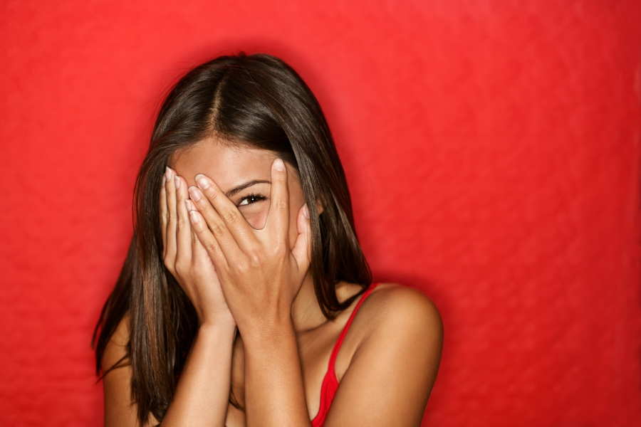 Shy teen girl in front of a red wall