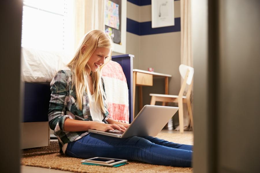 Teen girl in her bedroom working on her laptop