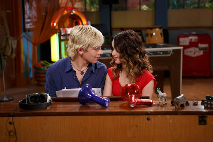 Austin & Ally about to kiss while sitting on a piano bench