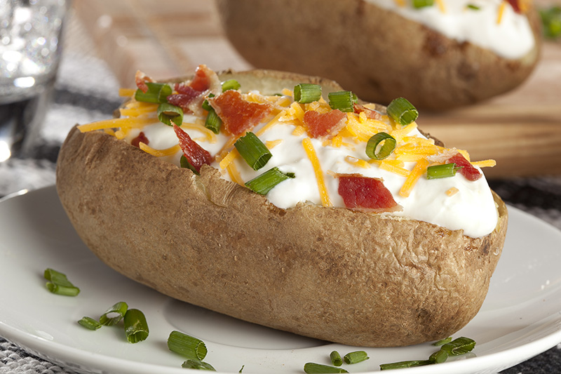 Baked potato topped with sour cream, cheddar cheese, chives and bacon