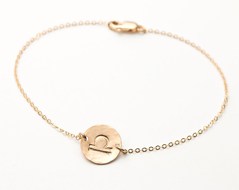Libra zodiac sign symbol on a simple gold bracelet
