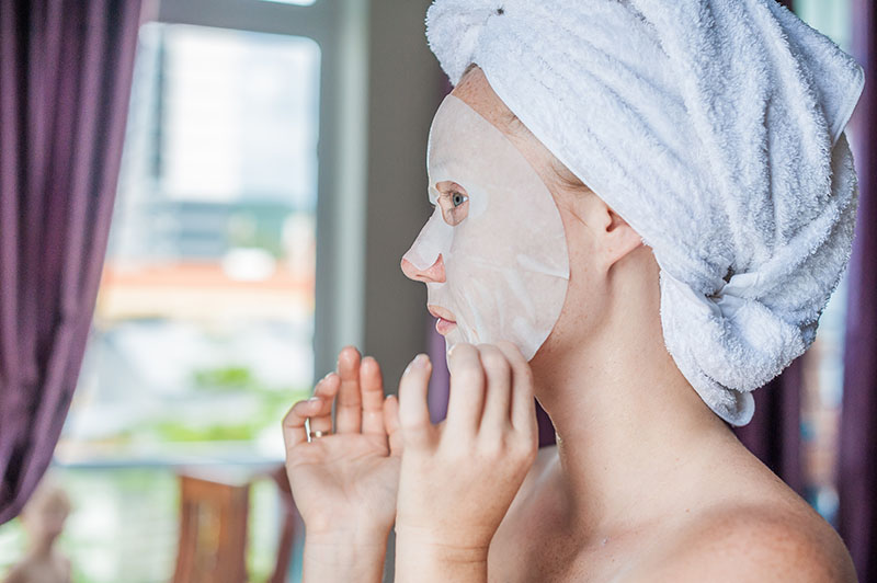 Girl applying a sheet mask while her wet hair is tied up in a towel