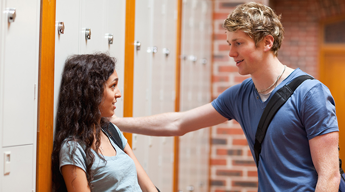 Girl talking to guy while leaning against locker