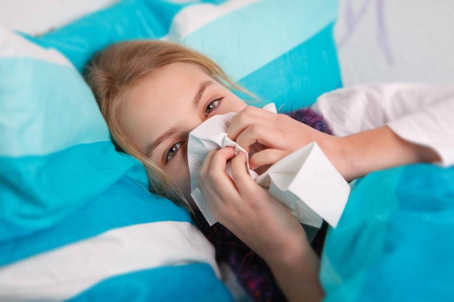 Girl lying sick in bed