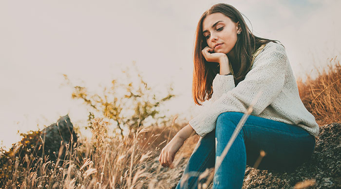Teen girl sitting in a field thinking