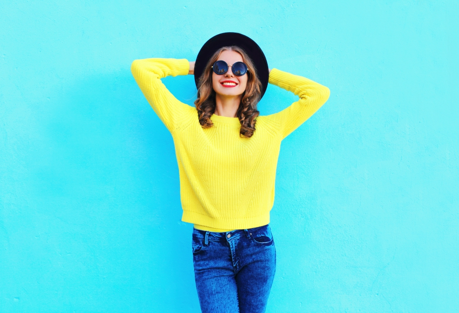 Girl with a hat and sunglasses on standing against a teal wall