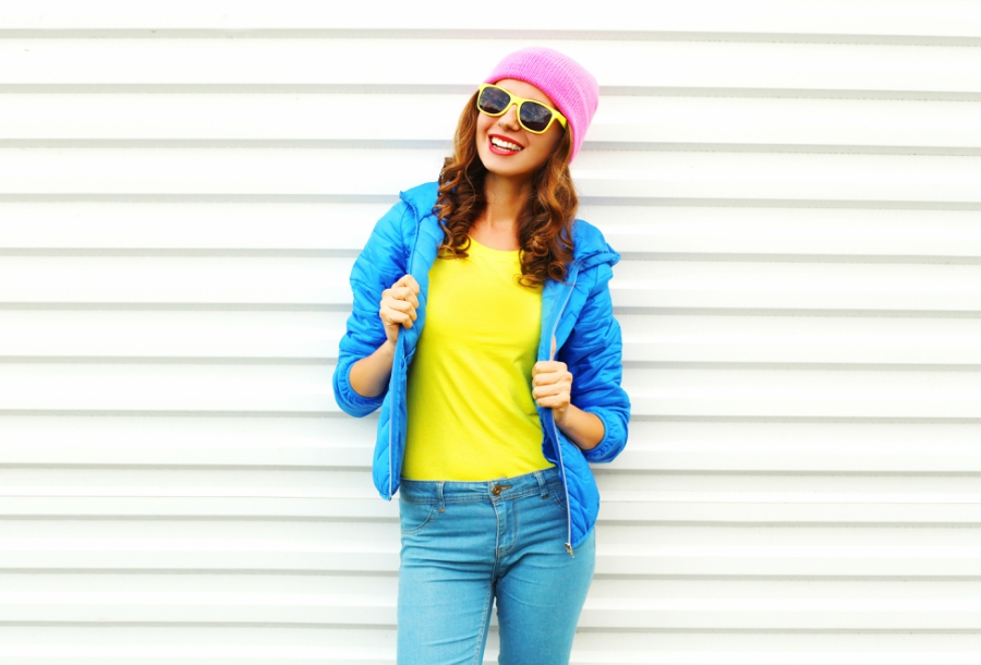Happy girl in sunglasses standing in front of a white wall