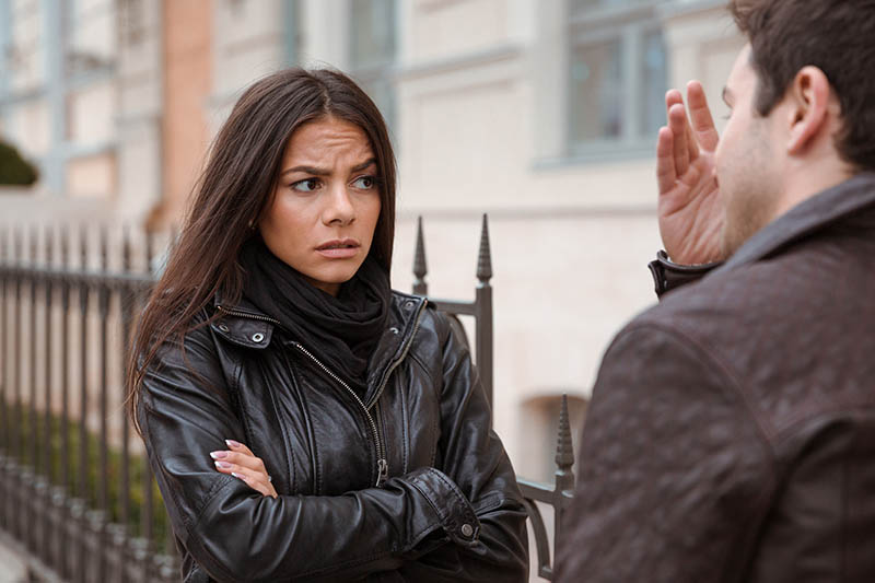Girl in a leather jacket looking irritated at a guy who's talking