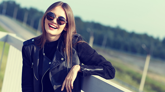 Girl in a leather jacket leaning on a fence and smiling at the camera