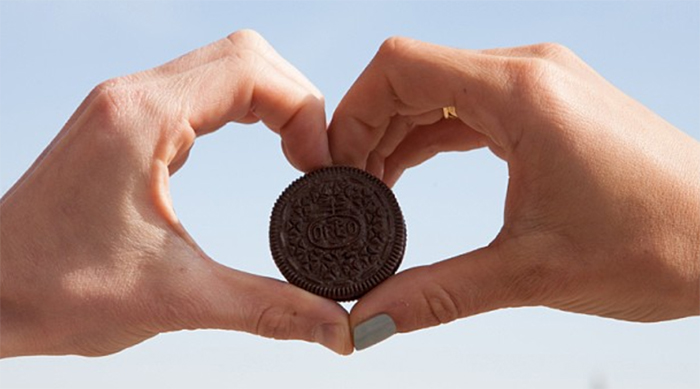 A couple holding an Oreo cookie in between their hands in the shape of a heart