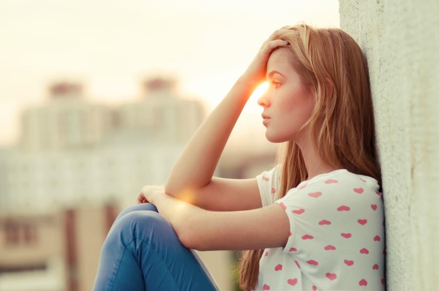 Sad teen girl resting against a wall