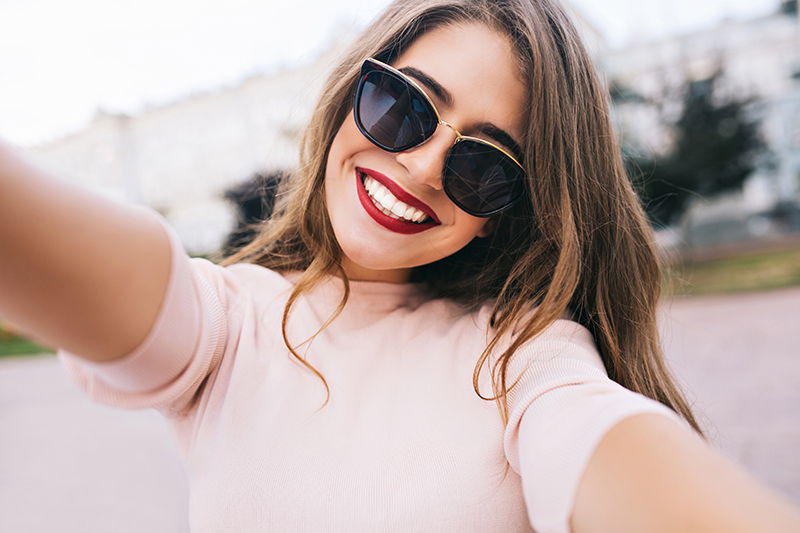Girl in pink blouse and red lipstick taking a selfie