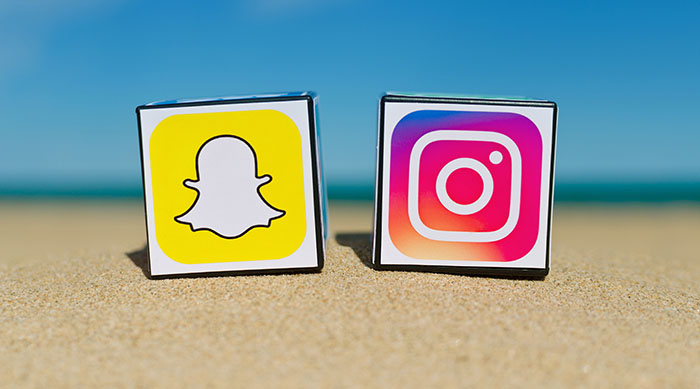 Snapchat and Instagram logos sitting on the beach