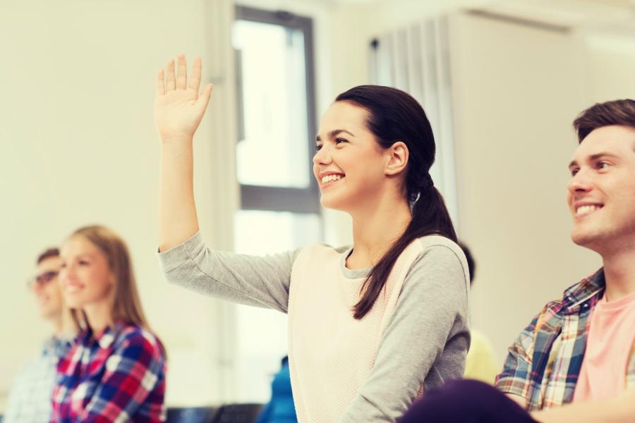 Teen girl raising her hand in class