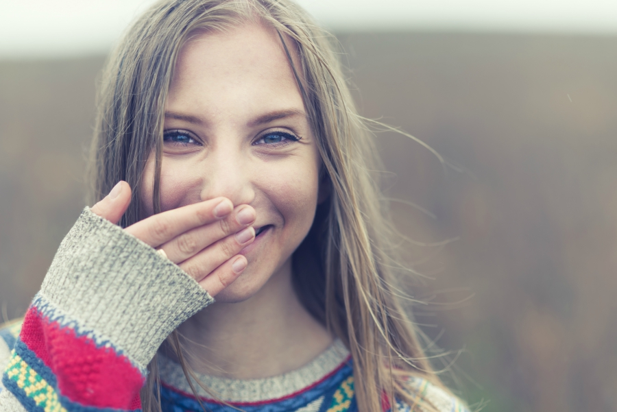Teen girl covering her mouth