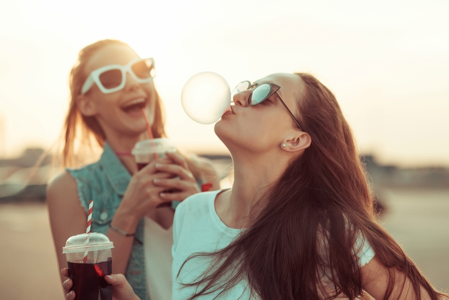 Teen girls hanging out and blowing bubbles with bubble gum
