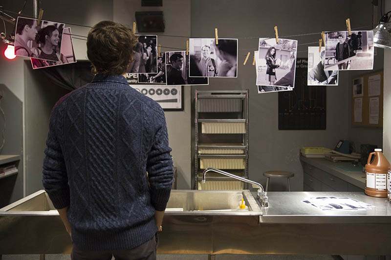 Tyler from 13 Reasons Why staring at the pictures he has taken in the school's dark room