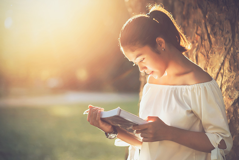 Girl reading a book while leaning against a tree