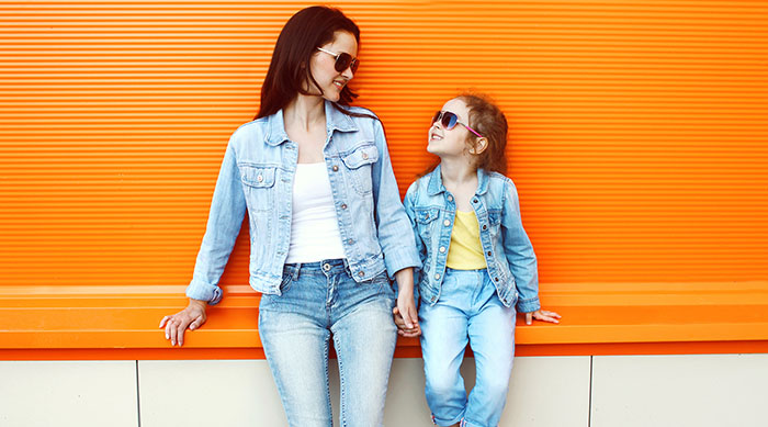 Young girl and her mom against an orange wall