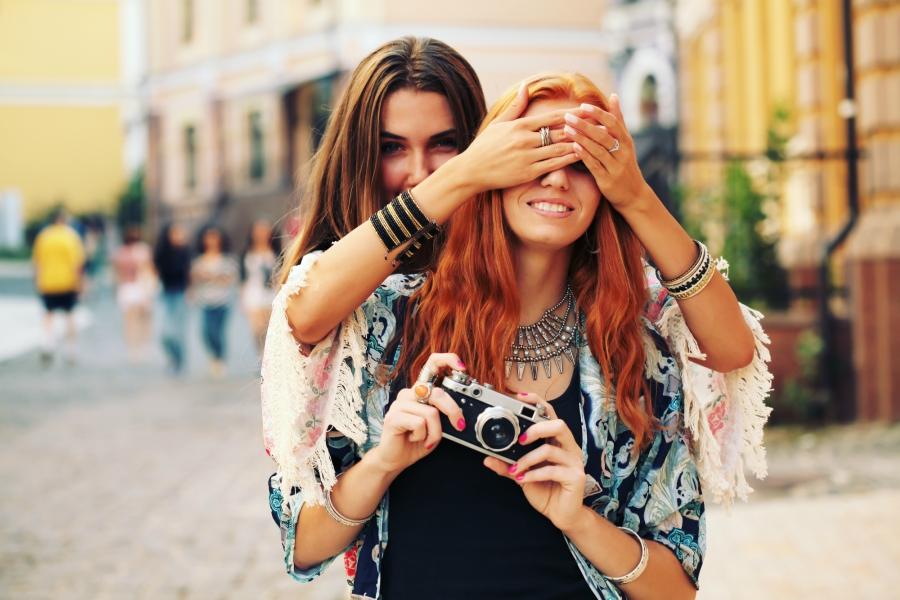 Teen girl blindfolding her friend