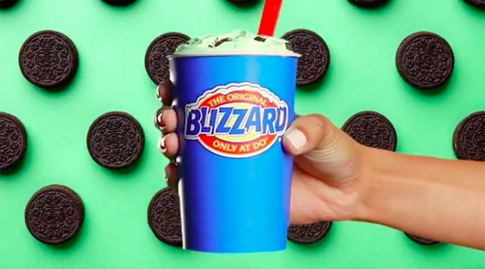 Person holding Mint Oreo Blizzard from Dairy Queen in front of a green backdrop with Oreos all over it