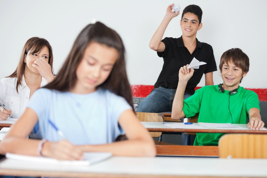 two boy bullies throw paper airplane at girl student in class