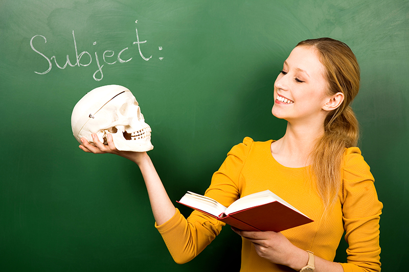 Girl reading Shakespeare while holding a skull in drama class