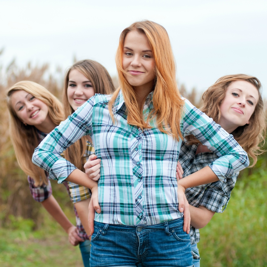 Four girl friends standing in a field