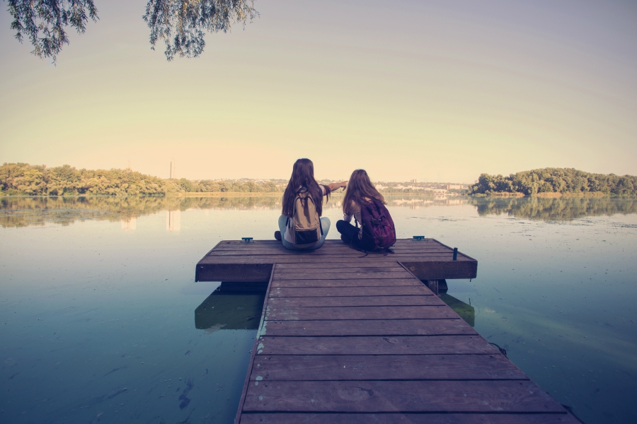 Two friends sitting on a lake