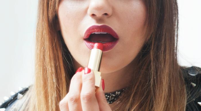 Girl applying a deep shade of red lipstick