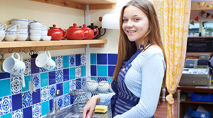 Teen girl working in a kitchen cleaning dishes