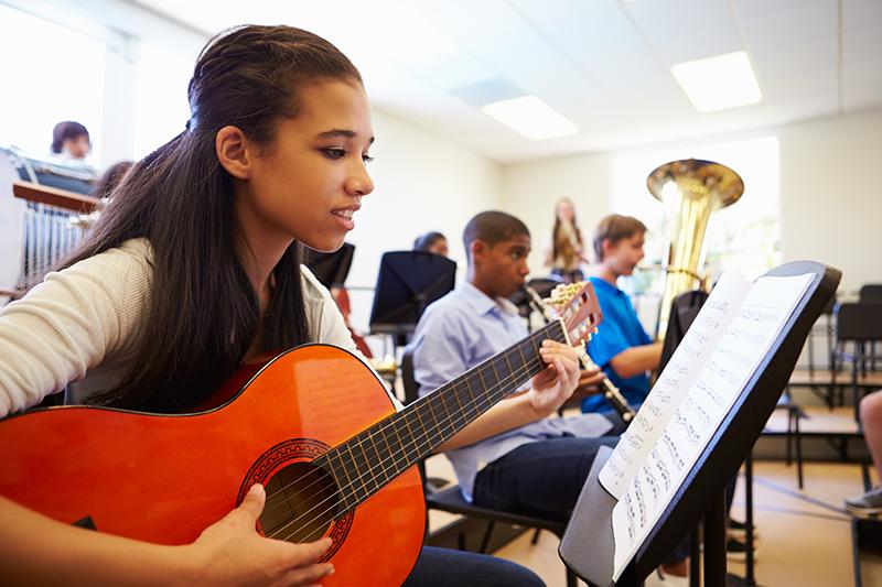 Girl playing guitar in music class