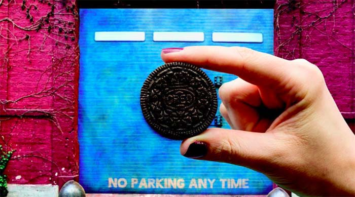 Girl holding Oreo in front of blue wall that reads 'No parking any time' on the bottom
