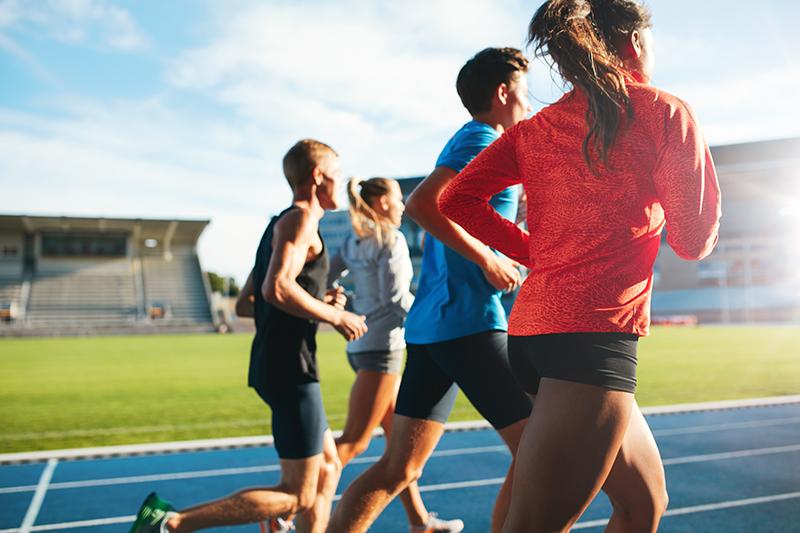 Girls and guys running on track