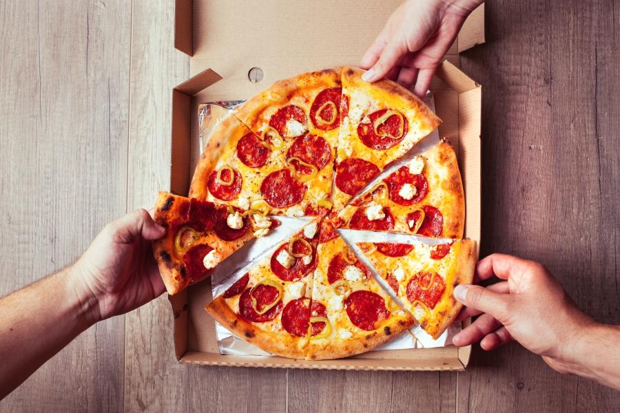 People grabbing pepperoni pizza