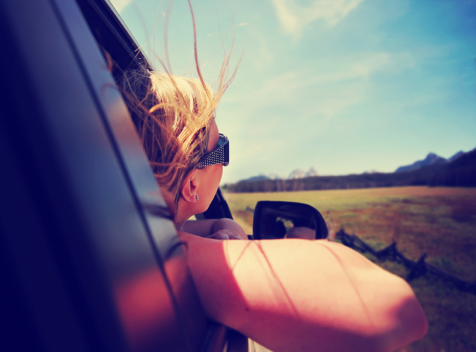 Girl with head out window of car on road trip
