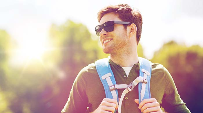 Guy hiking with sunglasses and backpack on