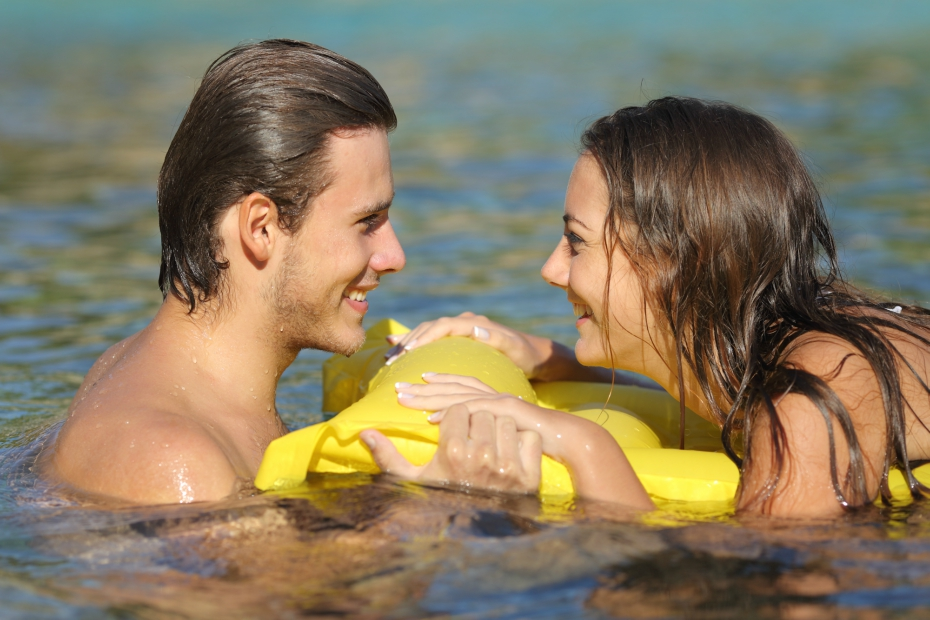 a boy and girl smile and flirt in a pool or ocean over a floatie