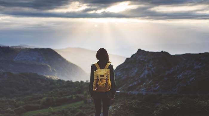 Girl with backpack on standing on the edge of a mountain top