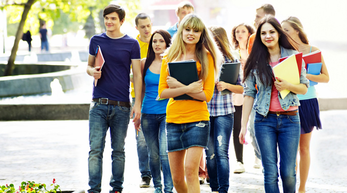 smiling teens are walking through campus holding notebooks during summer school