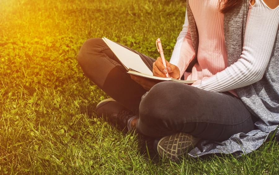 Teen girl journaling in the grass
