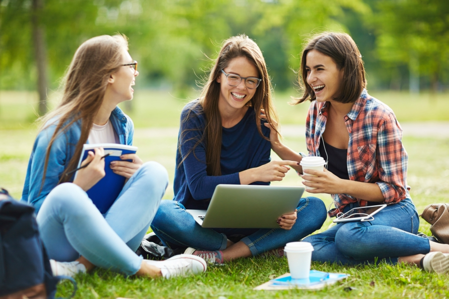 Three girls studying in the grass