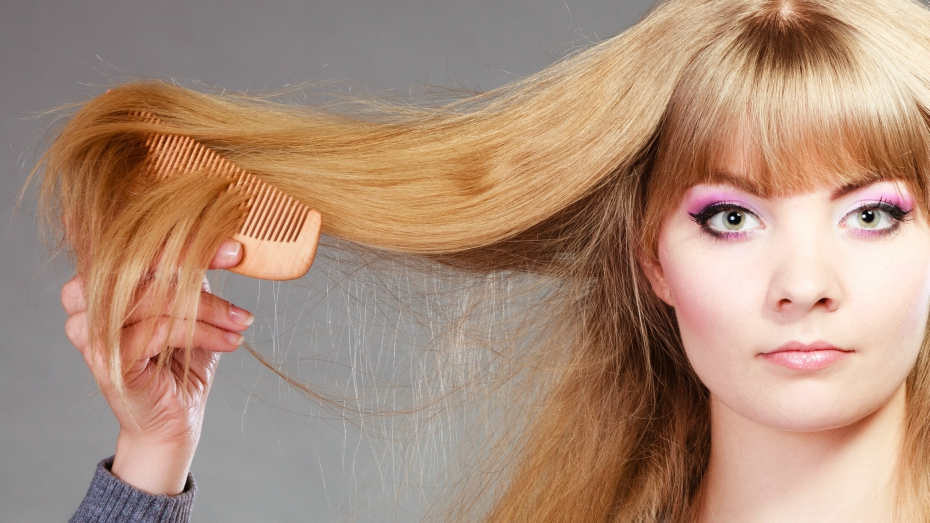 girl with long, blonde hair and bright pink eyeshadow combs her hair