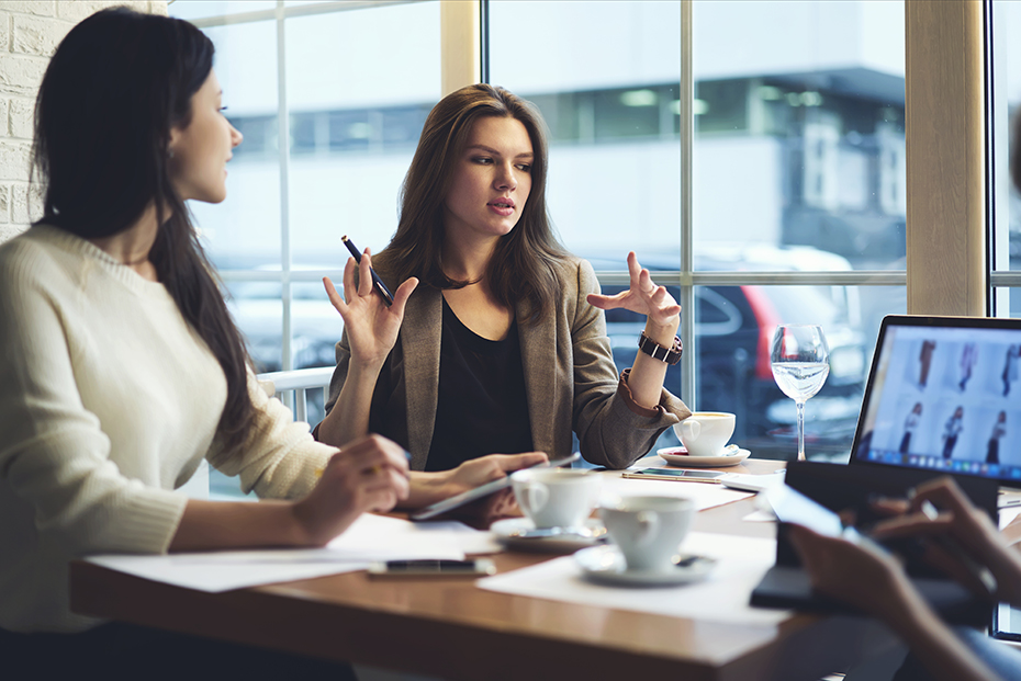 Women marketing leads of marketing experts working group explaining successful strategy for startup project to attract followers to online web store while having meeting with colleagues in cafe