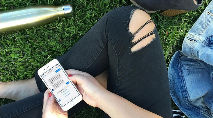 Girl using her phone in the grass