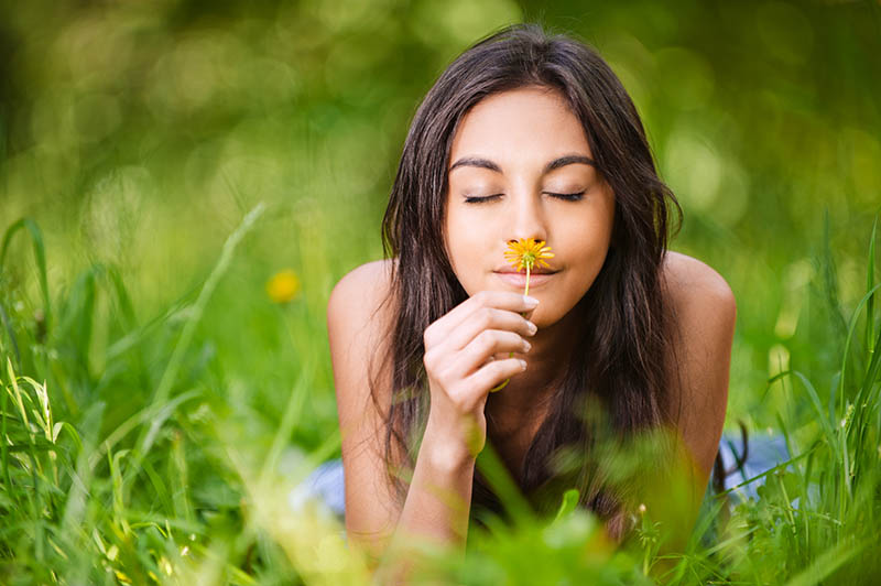 Girl sniffing a flower in a field