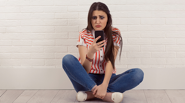 Girl looking sad while staring at her phone